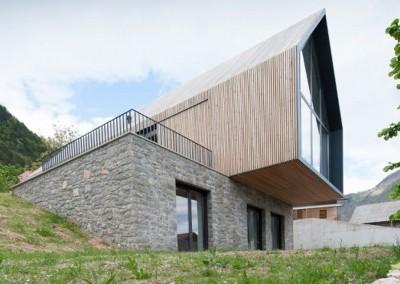 Na robu vasi v Tolminski kotlini je zrasla ena najbolj drznih arhitekturnih mojstrovin, ki jih je mogoče videti v Zgornjem Posočju. Stanovanjska hiša je izrazito inovativna v vseh pogledih tako z vidika arhitekturnega oblikovanja kot z vidika zasnove nosilne konstrukcije, uporabe materialov in rabe energije. Gre za zgled trajnostne gradnje v širšem Zgornjem Posočju in alpskem prostoru. Na željo investitorja je objekt zasnovan po zgledu tradicionalnih posoških senikov.