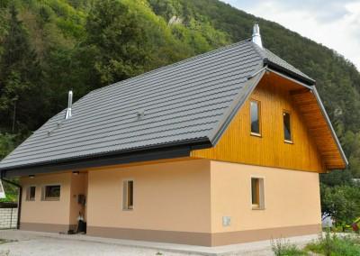 Ob zadnjem potresu na Bovškem je hišo naročnikov tako poškodovalo, da smo jo morali porušiti in na novo sezidati. Pritličje je zidano, nadstropje pa je zasnovano iz lesene konstrukcije. Končni izgled hiše povsem sovpada s tipično lokalno arhitekturo.